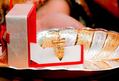 Golden ring in box on decorated tray. Golden wedding ring on a gold and silver tray. Presented to the bride or groom Stock Photography