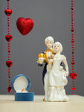 Golden ring in box for Valentines Day and porcelain figures of boy and girl. Box with a gold ring near the porcelain figures of a boy and a girl in the costumes Royalty Free Stock Photo