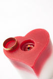 Golden ring and candle in the heart shape Royalty Free Stock Image