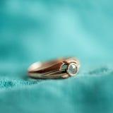 Golden ring closeup. Old golden ring on blue textile closeup, selective focus Stock Photos