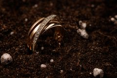 Golden ring with diamonds staying on a dark brown ground. Yellow golden ring with diamonds on a creative background of brown soil with small white balls and Royalty Free Stock Photo