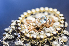 Golden ring with gem on pearl necklace stock photography