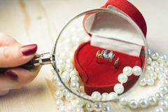 Golden ring with gem in a red gift box with pearls Stock Photo