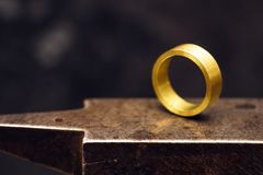 Golden ring on a goldsmith anvil in the jewelry factory, close u. P shot with copy space in the dark background, selected focus, narrow depth of field Stock Image