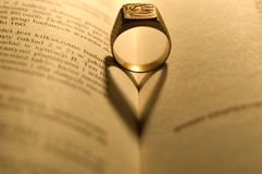 Golden ring in the open book Stock Photos