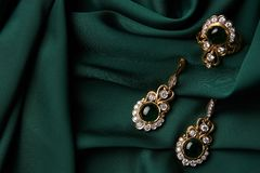 Golden ring and pair of earrings with green Emerald and Diamonds stock images