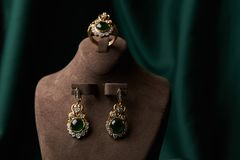 Golden ring and pair of earrings with green Emerald and Diamonds stock photos