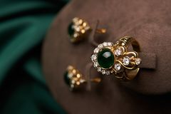 Golden ring and pair of earrings with green Emerald and Diamonds stock photo