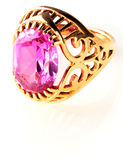 Golden ring with pink gem over white Royalty Free Stock Photography