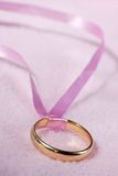 Golden ring with pink ribbon Stock Photo