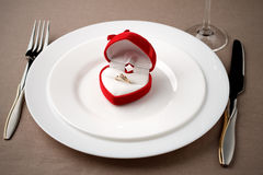 Golden ring in red case on white plate with fork, knife and glass. Royalty Free Stock Images