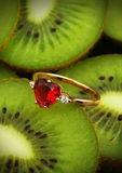Golden ring with red gem on colorful kiwi fruit background, vert Royalty Free Stock Photography