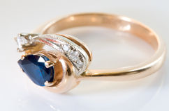 Golden ring with sapphire and diamonds Royalty Free Stock Photos