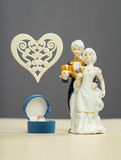 Golden ring for Valentines Day and porcelain figures of boy and girl. Box with a gold ring near the porcelain figures of a boy and a girl in the costumes of the Royalty Free Stock Images
