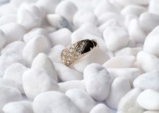 Golden ring on white pebbles Stock Image