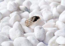 Golden ring on white pebbles Stock Image