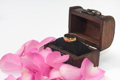 Golden ring in the wooden chest with pink rose petals Royalty Free Stock Photos