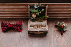 Golden rings in the beautiful rustic box and stylish men wedding accessories on the wooden background. Preparation for wedding concept. Horizontal Stock Photo