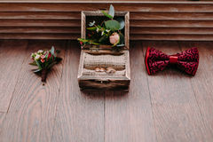 Golden rings in the beautiful rustic box and stylish men wedding accessories on the wooden background. Preparation for wedding concept. Horizontal Stock Photography