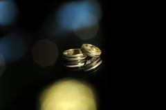 Golden rings on black glass Stock Photo