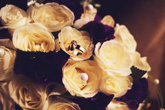 Golden rings on bouquet of roses Royalty Free Stock Image