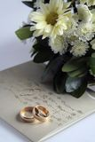 Golden rings, invitation and flowers. Picture of golden wedding rings, invitation and flowers Stock Photography