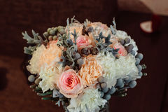 Golden rings lie on pink and beige wedding bouquet Stock Photography