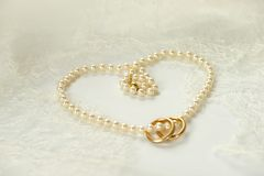 Golden rings on a pearl necklace heart. Heart of pearl necklace with two golden rings resting on white wedding lace Stock Image