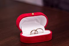Golden rings in a red box. On a table royalty free stock photos
