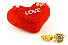 The golden rings and red heart. Royalty Free Stock Photography