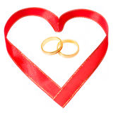 Golden rings in side a heart shape ribbon Stock Images