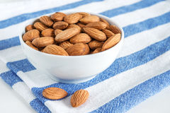 Golden roasted almonds in a white bowl. On a striped napkin Royalty Free Stock Image