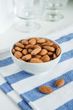 Golden roasted almonds in a white bowl. Golden roasted almonds in a white bowl on a striped napkin Stock Photo