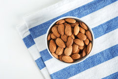 Golden roasted almonds in a white bowl. Top view. Golden roasted almonds in a white bowl on a striped napkin Stock Photos