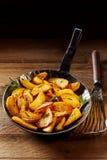 Golden roasted potato wedges with rosemary Stock Photo