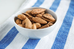 Golden roasted unpeeled almonds in a white bowl. Golden roasted almonds in a white bowl on a striped napkin Royalty Free Stock Images