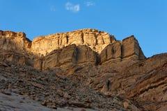 Golden rock in the desert at sunset Stock Images