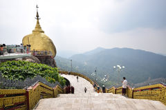 Golden rock on left and large stairs on right with hilly mountainous view in the background at Kyaiktiyo Pagoda Royalty Free Stock Photos