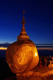 Golden Rock at twilight with praying people, KyaiKhtiyo pagoda, Stock Photo