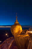 Golden Rock at twilight with praying people, KyaiKhtiyo pagoda Stock Photography
