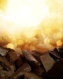Golden Rocks. A golden bokeh sunset behind a pile of rocks Stock Image