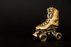 Golden roller skate against black background Stock Photo