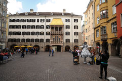 Golden roof museum and street artist. A street artist performing in front of The golden roof on the main historical square in Innsbruck.Austria Stock Images