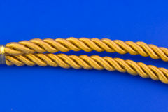 Golden rope. Isolated on blue background Stock Photography