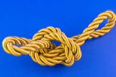 Golden rope. Isolated on blue background Stock Photos
