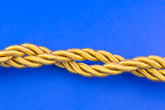 Golden rope. Isolated on blue background Royalty Free Stock Photo
