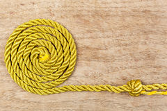 Golden rope on wooden background Stock Images