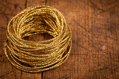 Golden rope on wooden table Stock Photos
