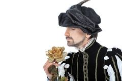 Golden rose. Portrait of a handsome man grandee in 16th century costume holding golden rose. Isolated over white background Stock Photos