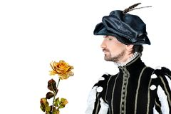 Golden rose. Portrait of a handsome man grandee in 16th century costume holding golden rose. Isolated over white background Stock Photo